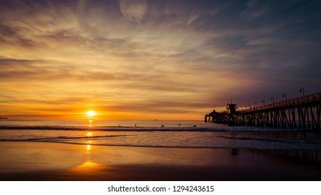 The setting sun at the pier in Imperial Beach, California with surfers swimming to catch waves.