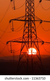 Setting Sun seen through an electricity pylon