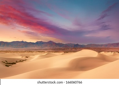 The setting sun sets the sky ablaze during a summer sunset on Mesquite Sand Dunes in Death Valley National Park.