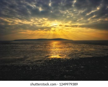The setting sun sinks over Brean Down in Somerset, UK