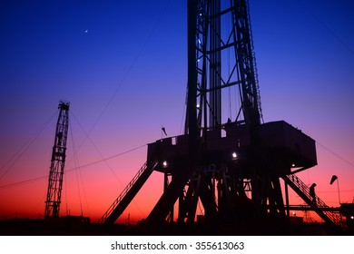 The setting sun under the oil derrick