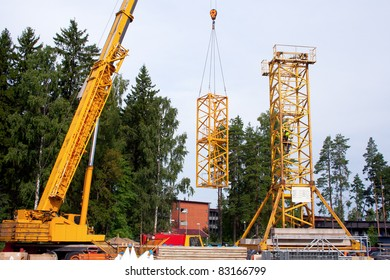 Setting up a tower crane in the construction site.  Tower mast is being built with the mobile crane.