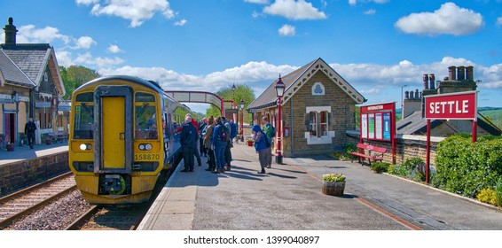 Settle, Yorkshire, UK - May 4th, 2019: Tourists at Settle Station wait to board the train to Carlisle, set to cross the famous Ribblehead Viaduct along their way