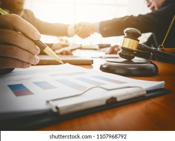 The settlement agreement shared between a businessman and lawyer by shaking hand, meeting in office room.