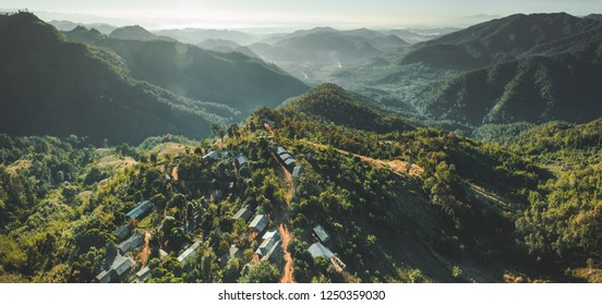 Settlement among Thailand wild nature. Aerial drone shot of green covered valley. Sunlit North Thai hills. Overwhelming Asian landscape. Buildings among the wild environment.