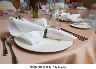 set-up dinner room in the hotel. folded napkin laid on plate on the table at restaurant