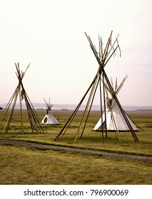 The setup structures of traditional lodging of North American First Peoples (Native Americans/American Indians) from Plains regions. Two completed; two with framework.