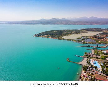 Sevan lake from aerial view. Turquoise water. Resort town. Sand beach. Ancient architecture. Caucasus mountains, Armenia