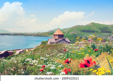 Sevanavank is a monastery in the province of Gegharkunik. Sightseeing in Armenia. View of Lake Sevan, green mountains and sky. Blooming field with yellow and white flowers, red poppies.