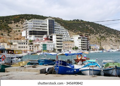 Sevastopol, Russia - September 22, 2014: pier of Balaclava bay with boats and yachts, view of mountain Tavros,    hotel at it foot on embankment