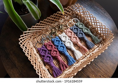 Seven (7) cotton macrame keychains are being displayed in a wicker basket beside a plant on an end table.