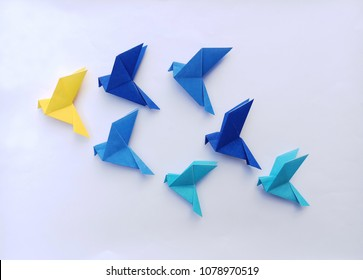 Seven blue origami  birds are flying leading by a yellow bird , isolated on white.