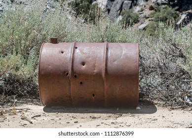 Seven bullet holes shot through a 55 gallon drum that may have been used as a fuel tank at Cabin Canyon Mine in Gold Butte National Monument, Clark COunty Nevada, USA.