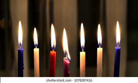 Seven candles  are burning  on light curtain background.