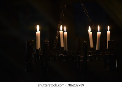 Seven candles in the interior. Seven white candle flames on black background.  Seven is lucky number and brings happiness.