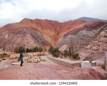 The Seven Colours Hill ( Cerro de los siete colores) at Purmamarca, Argentina. Young female tourist