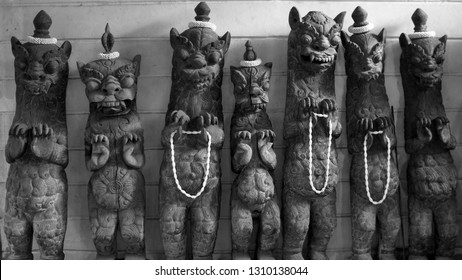 Seven Demonic Statues in Black and White Holding Garlands and Sporting Topknots