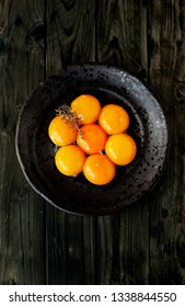 Seven Egg Yolks on a black rustic plate with a Sprig of Thyme (Thymus Zygis variety) over a wooden table.