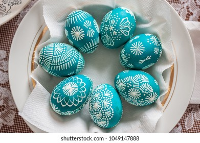 Seven emerald Easter eggs in a plate. Close up, soft focus, painted with wax and food colors. Easter holiday concept. Homemade, handmade, top view.