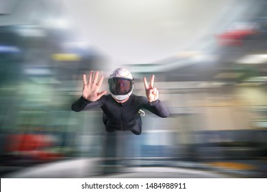 Seven.Men fly in white helmet and black suit and show 7 fingers. Numeral 7.  Indoor skydiving in wind tunnel.