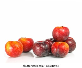 seven fresh and crunchy victoria plums on white