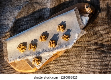 Seven halves of the walnuts on the sackcloth serviette on the wooden desk and sackcloth with its shadows