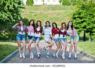 Seven happy and sexy girls on short shorts posed and having fun on road at park on bachelorette party