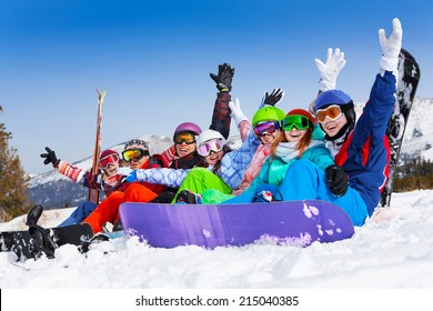 Seven happy smiling friends wearing ski mask sitting together lifting hands up in the air on the mountains background
