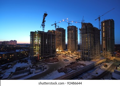Seven high buildings under construction with cranes at evening