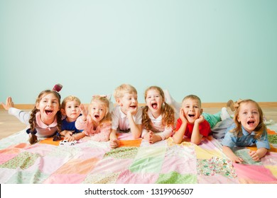 Seven laughing kids laying on a floor