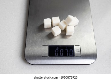 Seven lumps of refined sugar are weighed on a kitchen scale. Diet.
