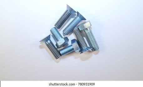 seven metal bolts on white background