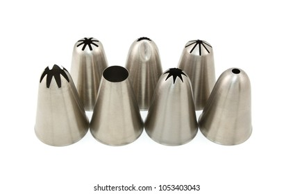 Seven metal icing nozzles for piping different shapes, arranged in two rows on a white background