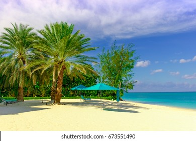 Seven Mile Beach in the Caribbean with its palm trees and parasols, Grand Cayman, Cayman Islands