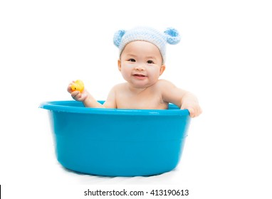seven month old Asian baby in Bathtub and she play yellow duck on white background