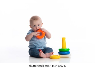 A seven month old baby boy playing with a ring stack toy. Shot in the studio on a white,  backdrop.
