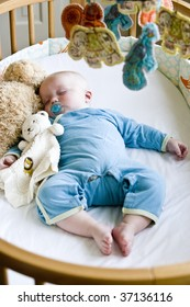 Seven month old baby boy sound asleep in his crib