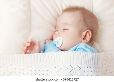 Seven month old baby sleeping on white blanket and pillow. Sleepy child on soft bedding with pacifier