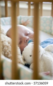 Seven month old baby sound asleep in his crib