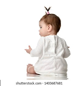Seven month old infant baby girl toddler sitting backside view isolated on a white background