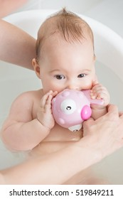Seven months old baby girl in a bath, playing with pink toy and mothers arms around her, washing her