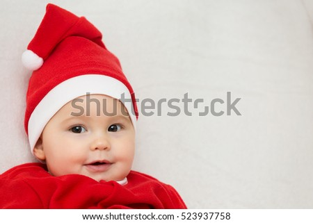 66bd49c8e9ad Seven months old baby girl in Santa Claus dress sitting on a white blanket,  looking