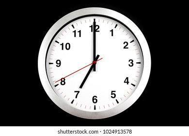 it's seven o'clock already, time to wake up for breakfast, modern white metallic alarm clock on black background