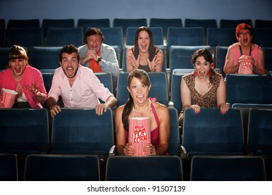 Seven people screaming and scared in a movie theater