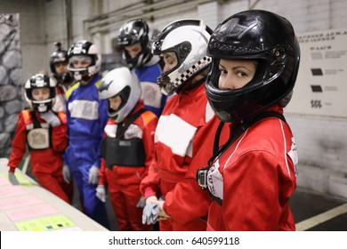 Seven people (three adults and four children) in helmet listen to lesson on instruction before karting, focus on right woman