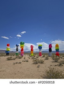 Seven pillars made of neon colored boulders stand against a barren desert background