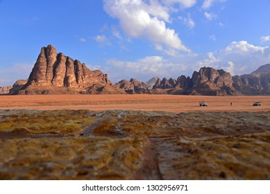 The Seven Pillars of Wisdom with blue sky background.Whire car in red Wadi Rum dessert.Dream destination for traveller with copy space for design work.Nature Background.