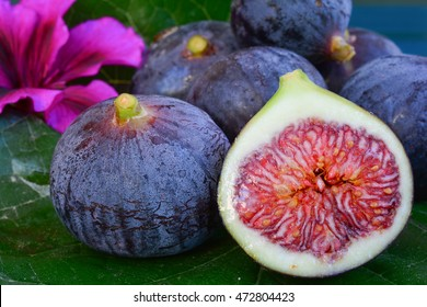 Seven ripe blue figs on big mulberry leaf on blue wooden table, side view