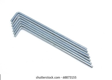 Seven round metal tent pegs on white background