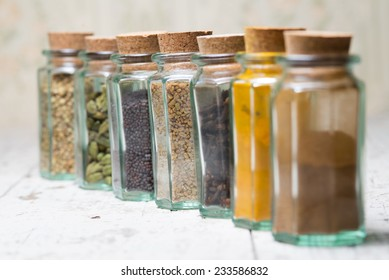 Seven in a row indian spices in tiny vintage glass bottles  with cork ,isolated